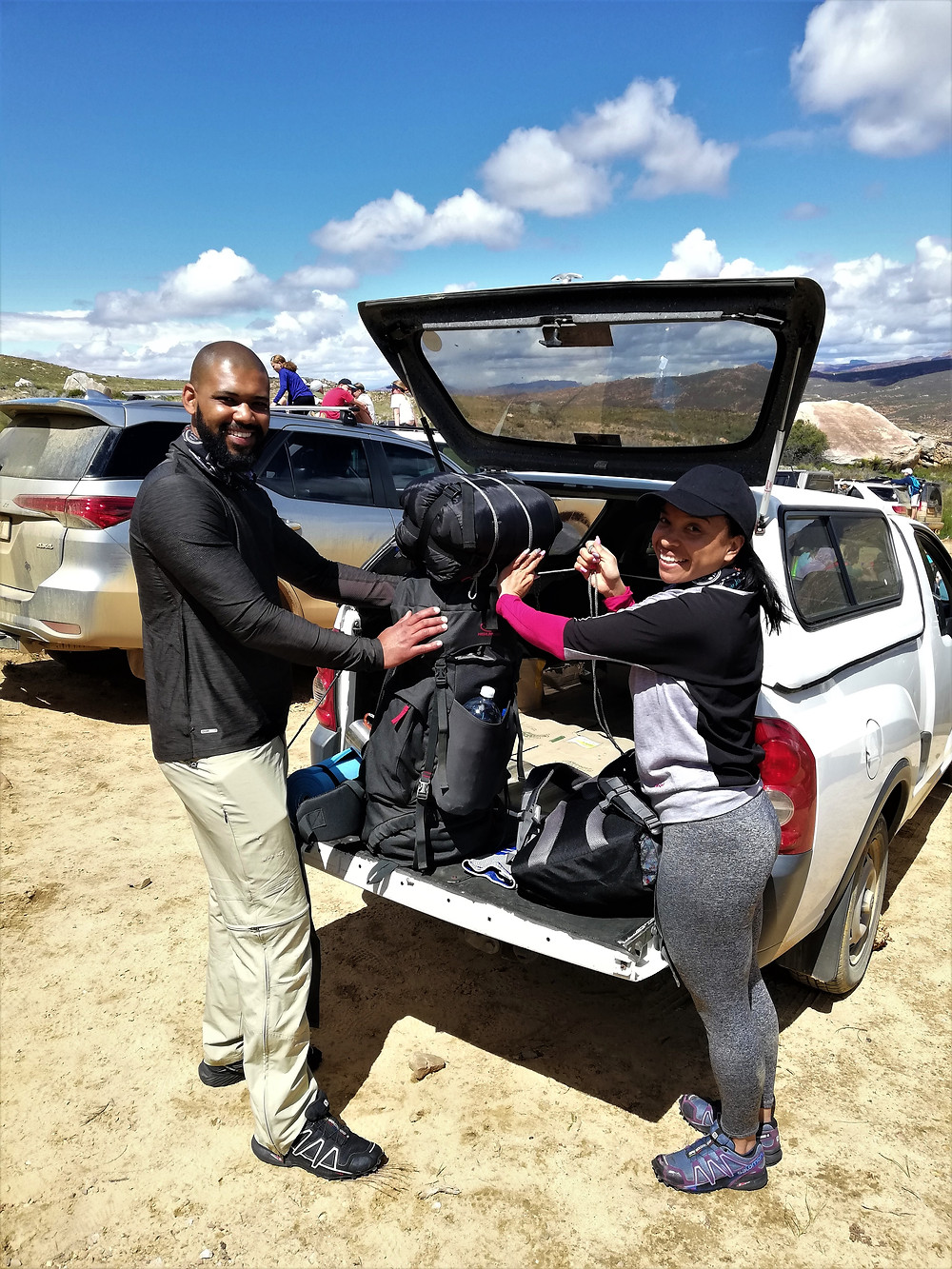 A man and a woman holding a backpack on the tailgate of a small utility vehicle