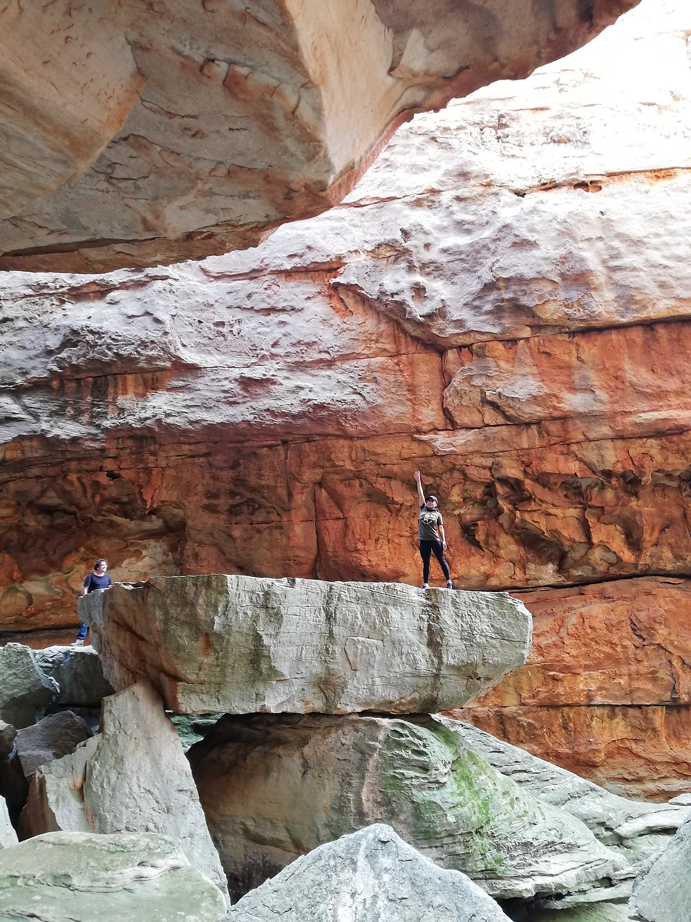 A woman standing stretching towards the ceiling of a large rock chamber