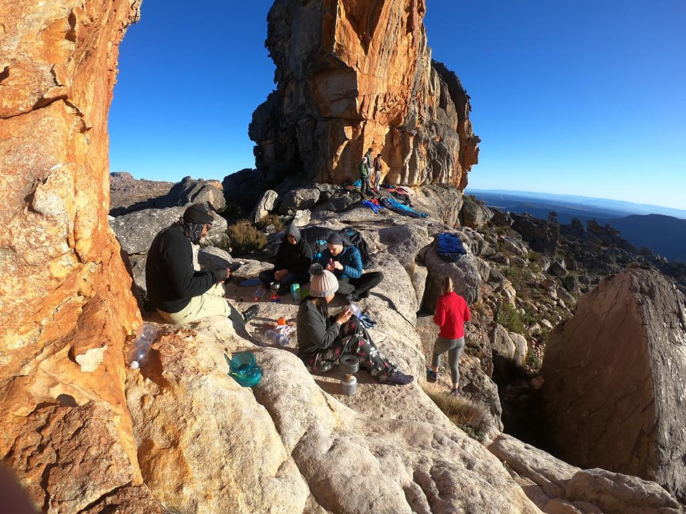 A group of people sitting on the rocks in the morning sun, under an arched rock formation, making breakfast with camping stoves