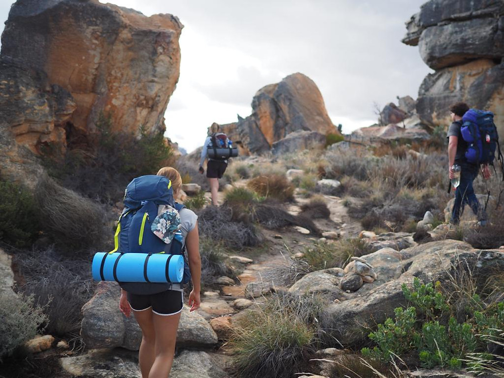 Three hikers with backpacks making their way through a rocky landscape