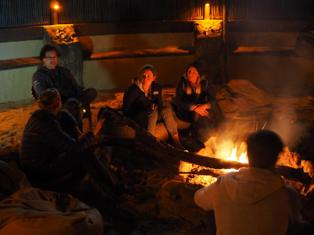 Five friends sitting around a fire in a fenced boma