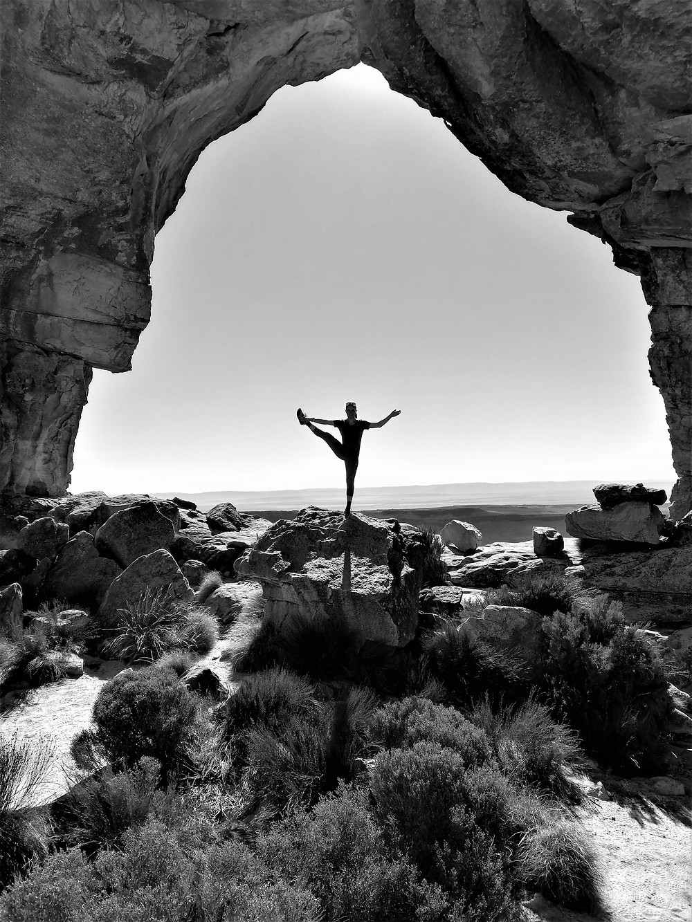 A woman posing with one leg held in the air, under an arched rock formation
