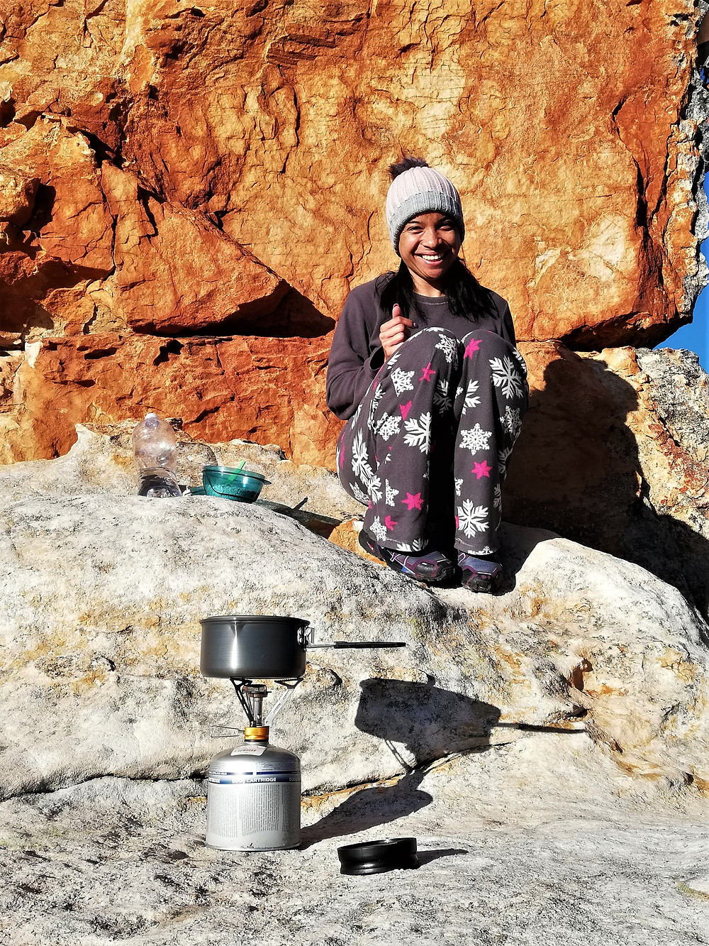 A smiling woman sitting on a rock in front of a rock face with a camping stove in the foreground