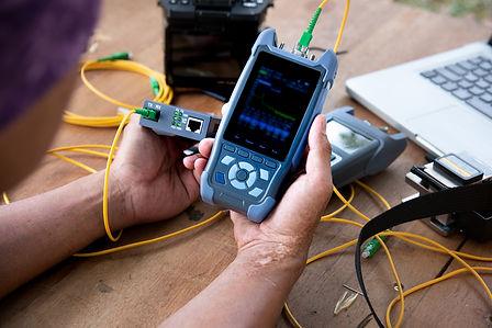 master's hands with optical fiber tester, OTDR meter.jpg