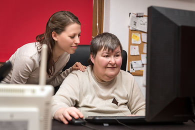 Caregiver And Mentally Disabled Woman Learning At The Computer.jpg