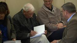 Veteran Keith Norrish signs a copy.