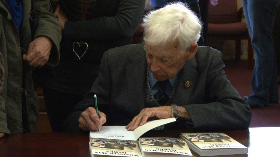 Veteran Jim McKenzie signs copies.