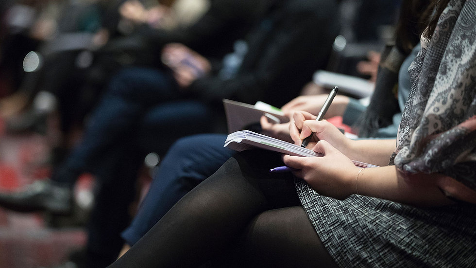 Audience taking notes at leadership expert event