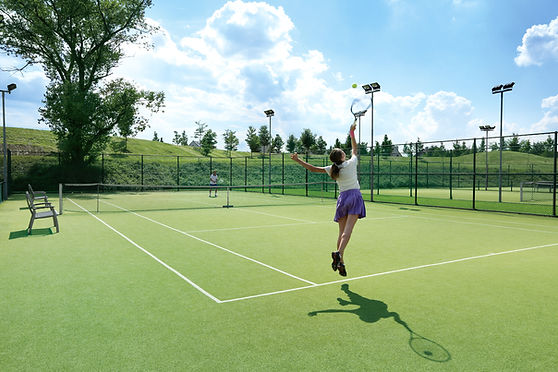 Frau serviert Tennisball