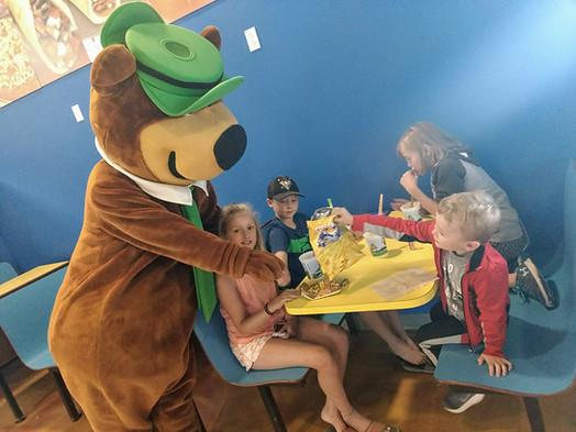 Yogi Bear trying to eat Josie's lunch
