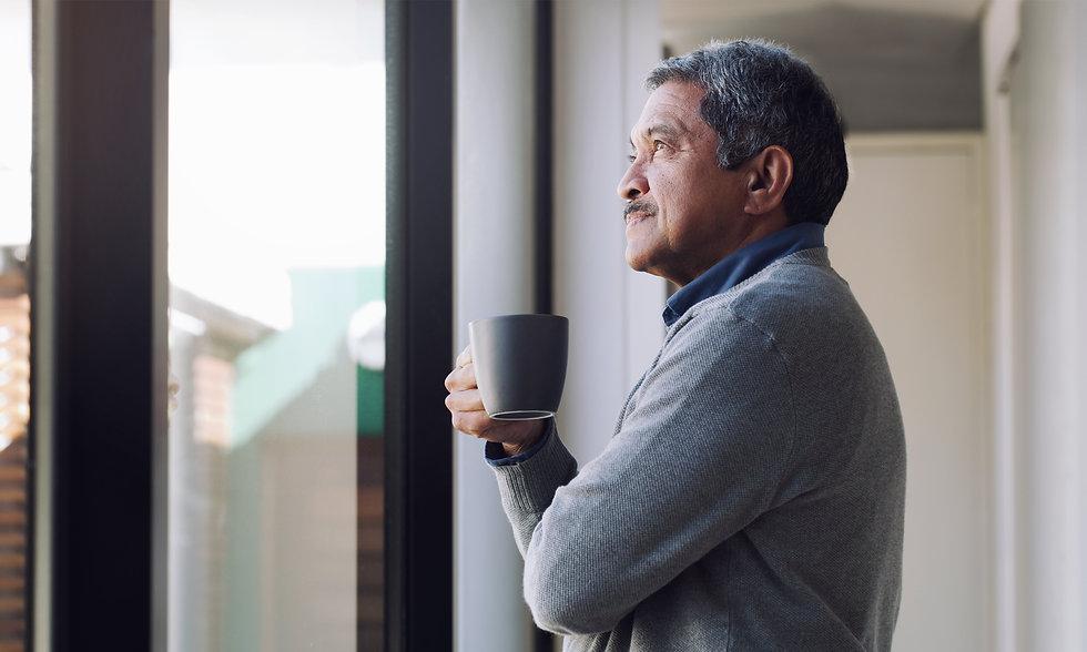 mature man at window - iStock-1283630223