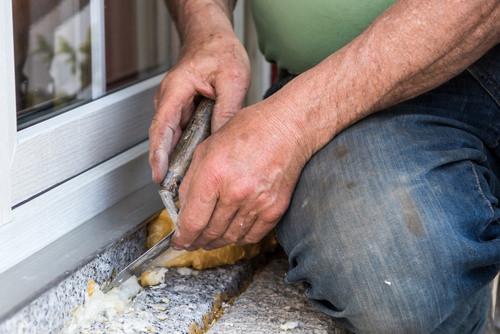 man fjerner byggskum fra en vinduskarm