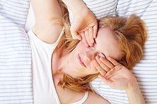 kvinne som våkner, seng, naturmaterialer