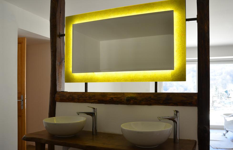 Miroir lumineux monté sur structure métallique pour créer une séparation architecturale élégante. Au dos du miroir lumineux se trouve un miroir simple à glace biseautée.