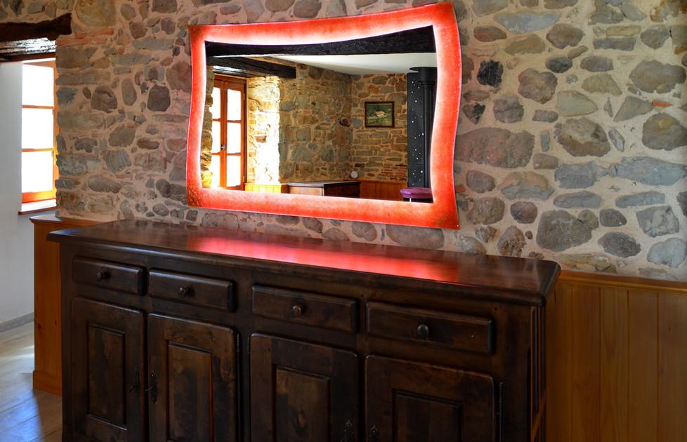 Miroir lumineux en forme de vague déferlant sur les galets de ce salon rustique!