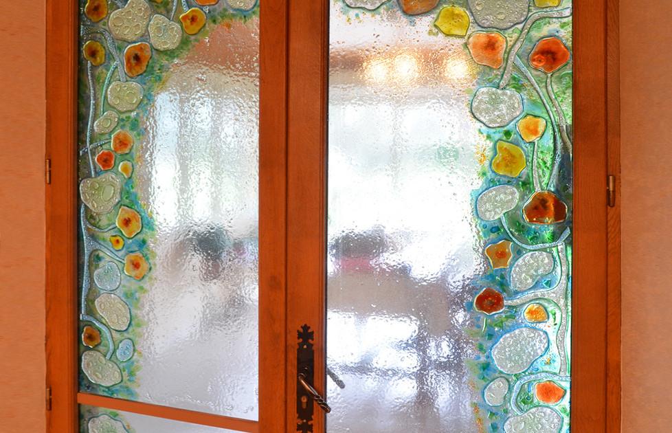 Ce vitrail en verre fusionné monté sur double-porte, crée une douce et unique transition architecturale.