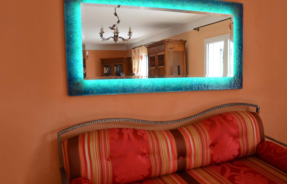 Un miroir lumineux à dominance bleue pour joyeusement jouer avec les tons automnaux de ce salon.