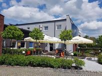 Ogródek piwny z rozstawionymi stołami i parasolami