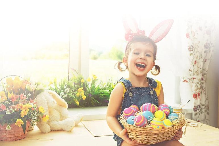 Uśmiechnięte dziecko z koszykiem pełnych jajek