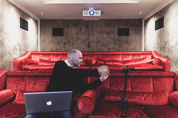 Wayne Hyde calibrating home cinema sound with a laptop and microphone