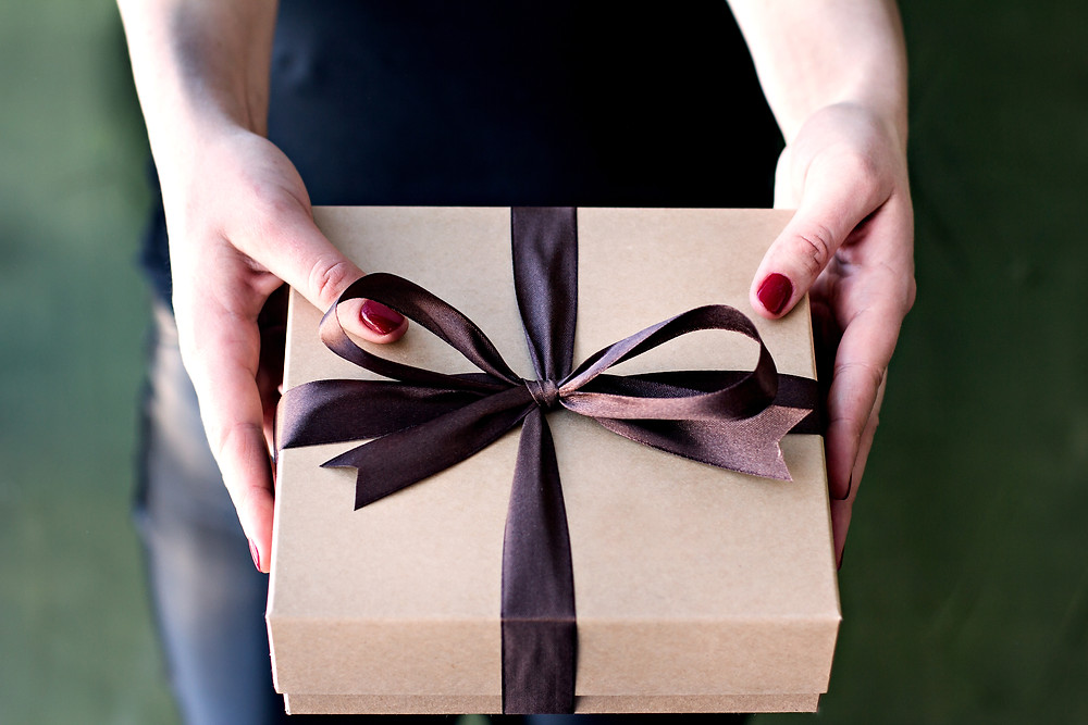 Woman holding gift box wrapped in brown ribbon