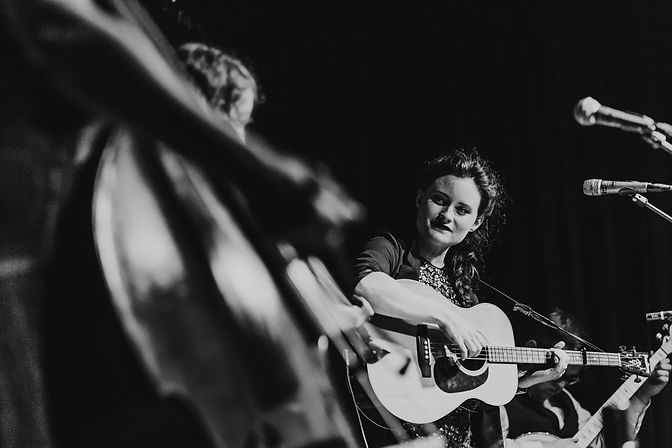 Black and white photo of Rosie Hood playing tenor guitar at Sheffield album launch gig