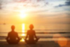 Young yoga couple meditating during amaz