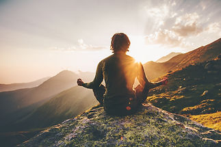 Man meditating yoga at sunset mountains