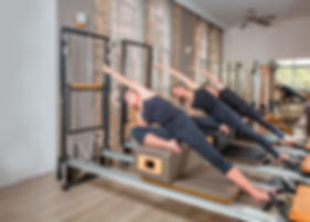 Young women exercising on pilates reform