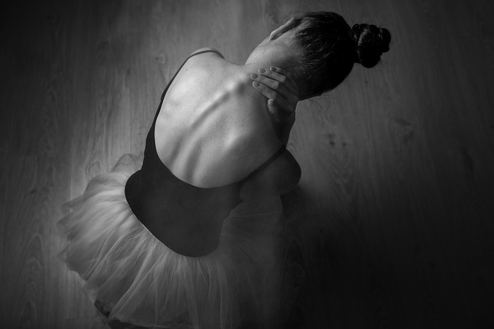 Black & While photo taken looking down on a dancer who wearing a short light colored tutu with a black leotard and is bent over slightly holding neck.