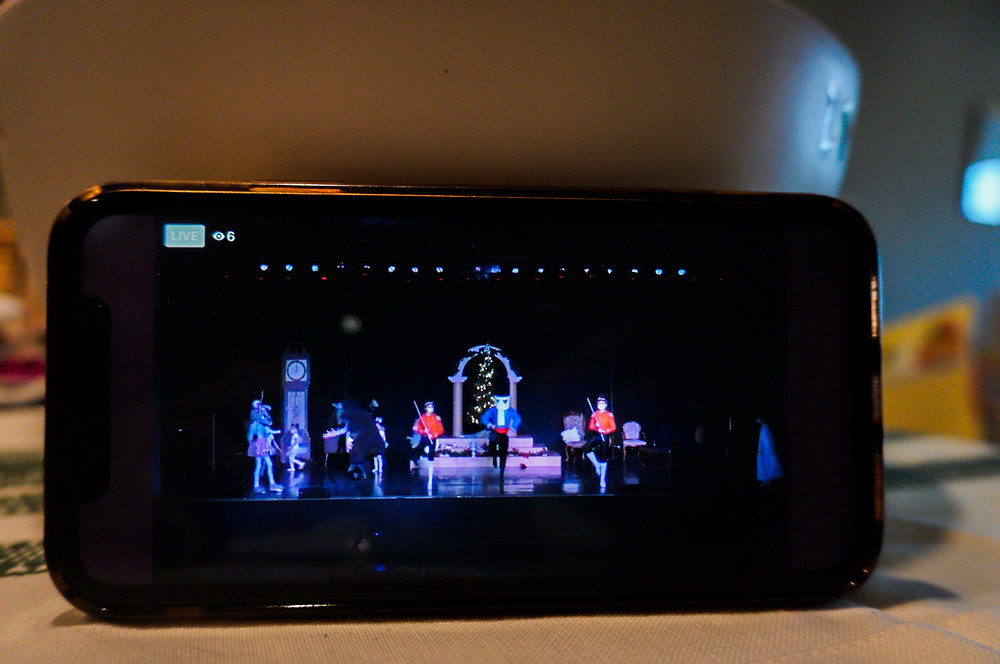 Phone placed on table leaning against white bowl, playing the live feed of The Nutcracker by Rise Up School of Dance during the battle scene of the performance with the Nutcracker performer in the middle.