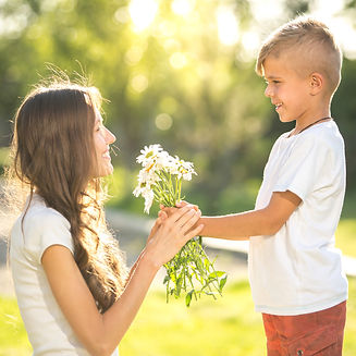 Little boy give flower present to her mo