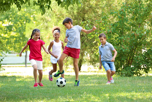Cute children playing football in park.j