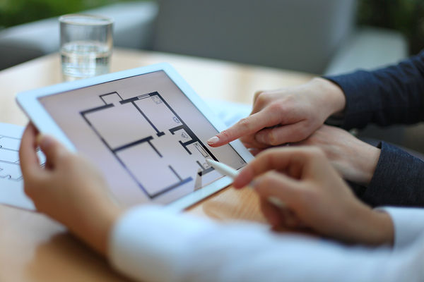 Real-estate agent showing house plans on