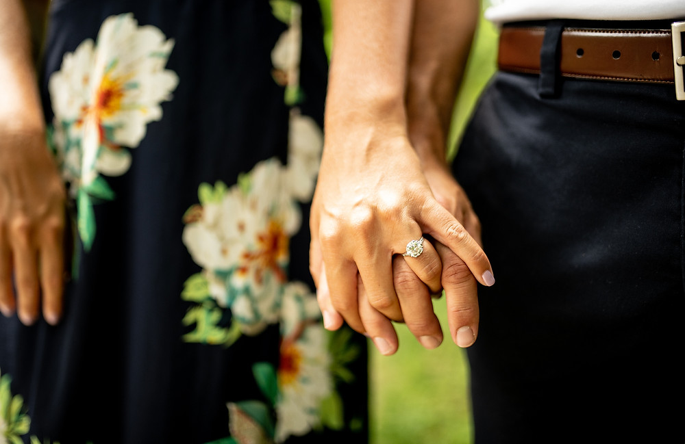 Man and woman's hands with solitaire engagement ring