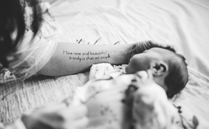 black and white photo of mom's tattoo and baby