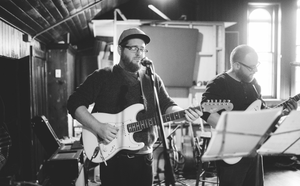 black and white photo of guitarists playing in band