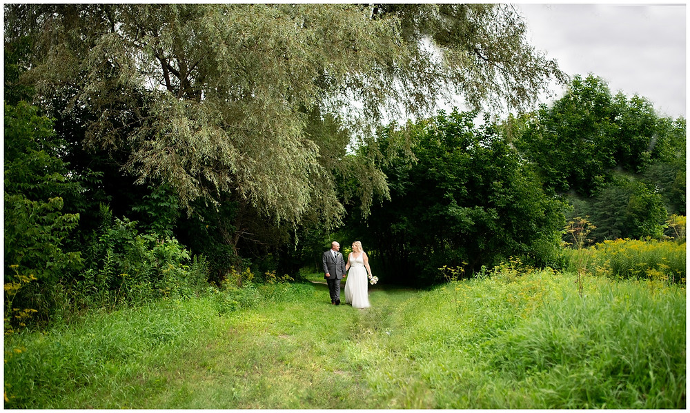 bride and groom walk together underneath a giant willow tree