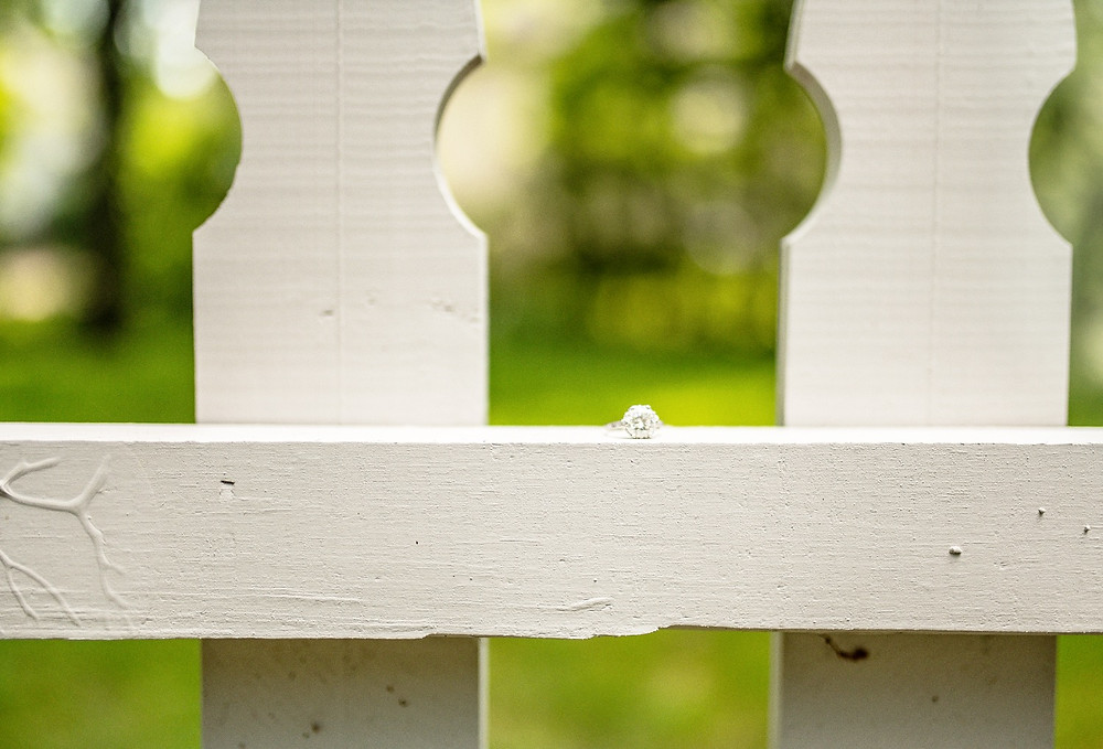 Solitaire engagement ring sits on a white picket fence in Hudson, Ohio
