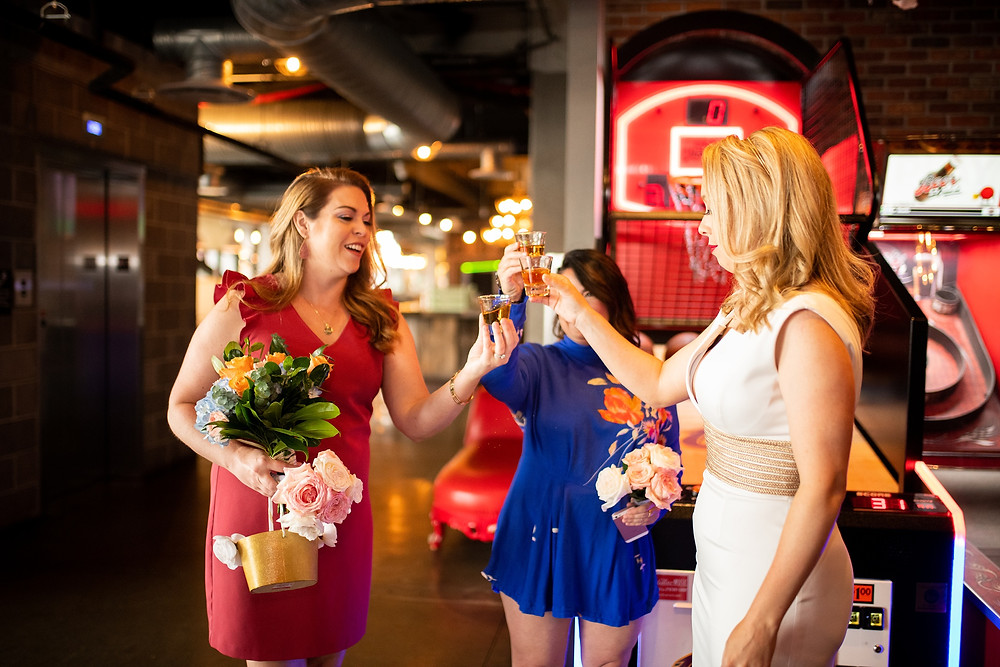 bride and bridesmaids take a shot in punch bowl social in cleveland ohio