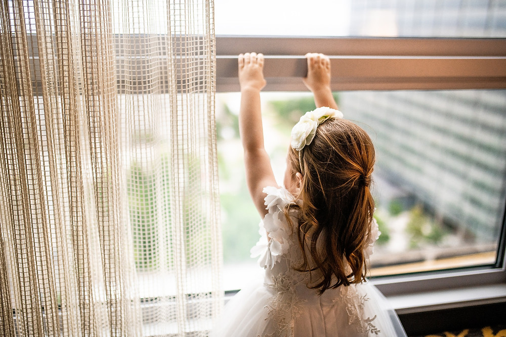 little flower girl hangs on window of the westin cleveland