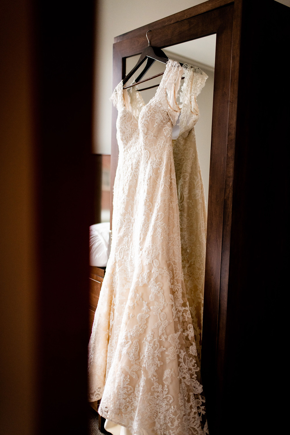 blush and lace wedding dress hanging at a hotel near Cleveland Ohio