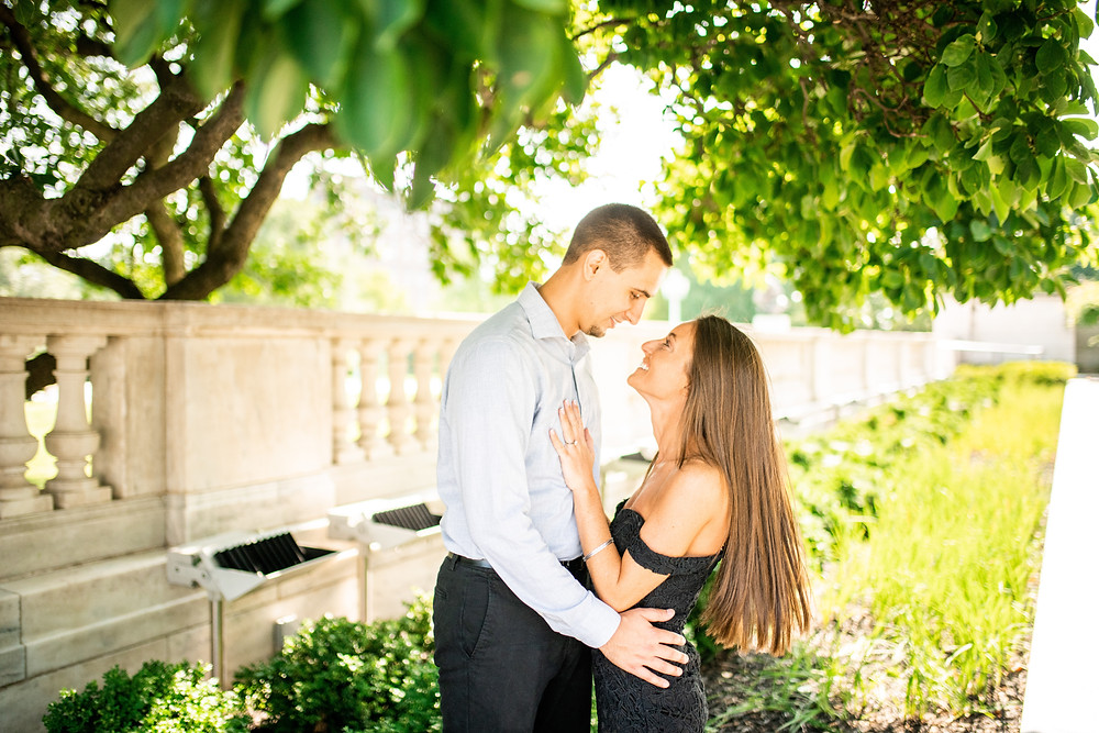 Woman and man smile at each other under a tree at an engagement session at Cleveland Museum of Art