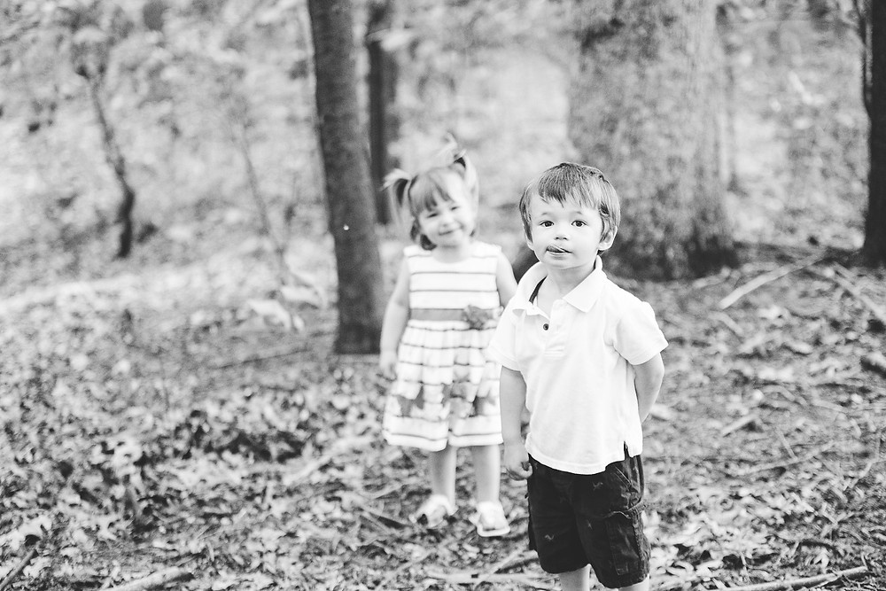 Little boy and girl standing in the woods, the little boy has his tongue out.