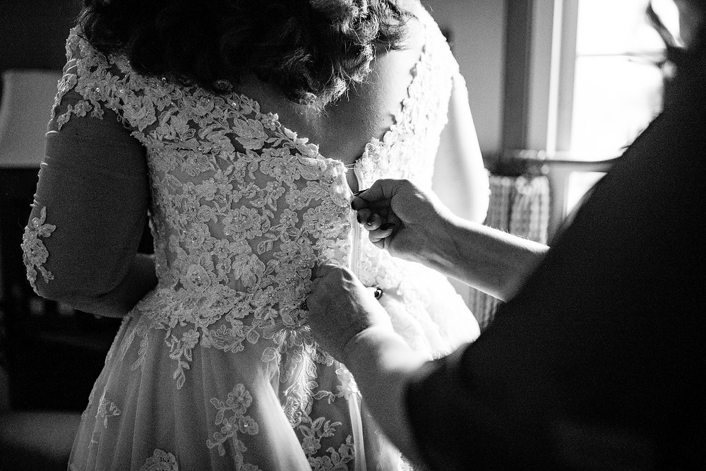 mom zips up dress for bride at wedding in cleveland ohio