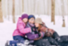 snowy family hugging together in a forest