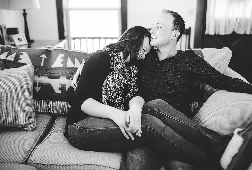 black and white photo of man and woman cuddling on a couch