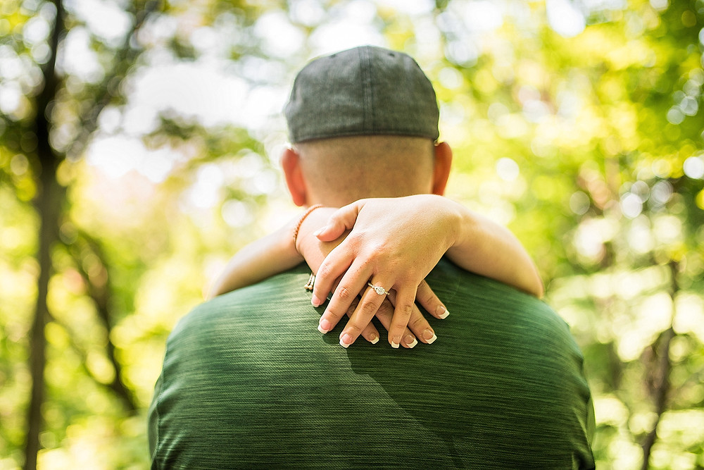 Woman wraps her hands around man's shoulders with engagement ring showing at Whipps Ledges in Hinckley, Ohio