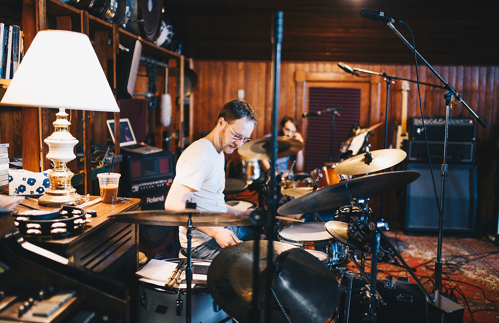 band member playing drum set in studio setting