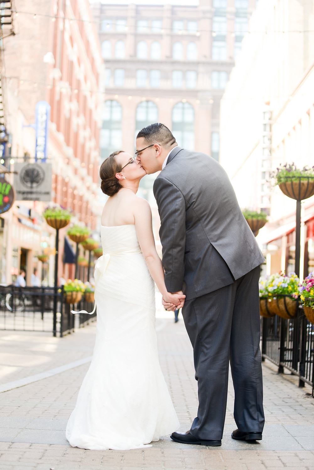 Bride and groom kiss standing on East 4th Street in Cleveland, OH